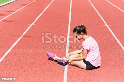 Female athlete with pain in knee joint on running track on stadium, sunny day