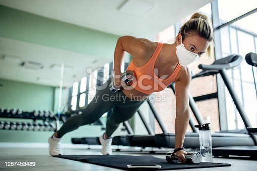 Athletic woman lifting weights in plank pose while wearing protective face mask at health club.