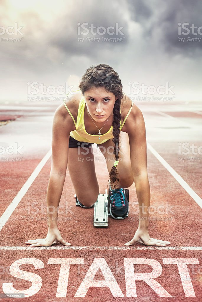 Female athlete with yellow too in the starting blocks stock photo