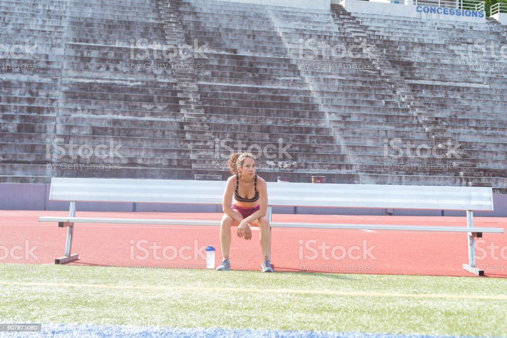 Female athlete working out at stadium field stock photo