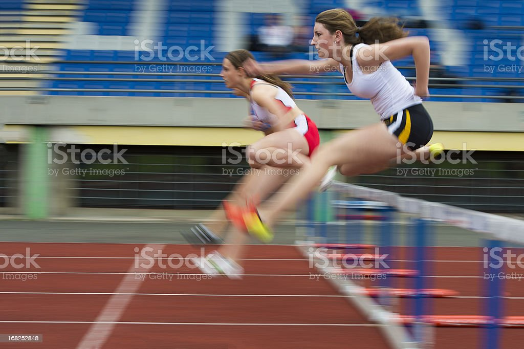 Female athletes at hurdle race 100 m stock photo