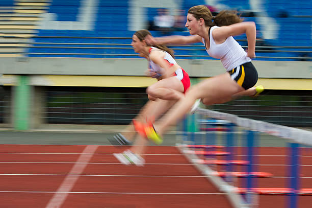 Female athletes at hurdle race 100 m Young female athletes at hurdle race 100 m, panning, motion blurred, selective focus women's track stock pictures, royalty-free photos & images