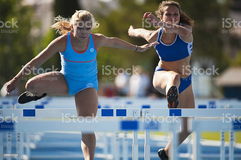 Female athletes at hurdle race stock photo