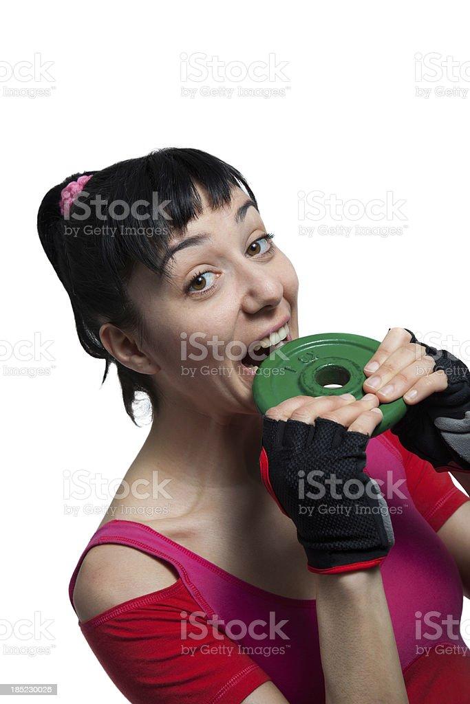 Female athlete's biting a dumbbell disk stock photo