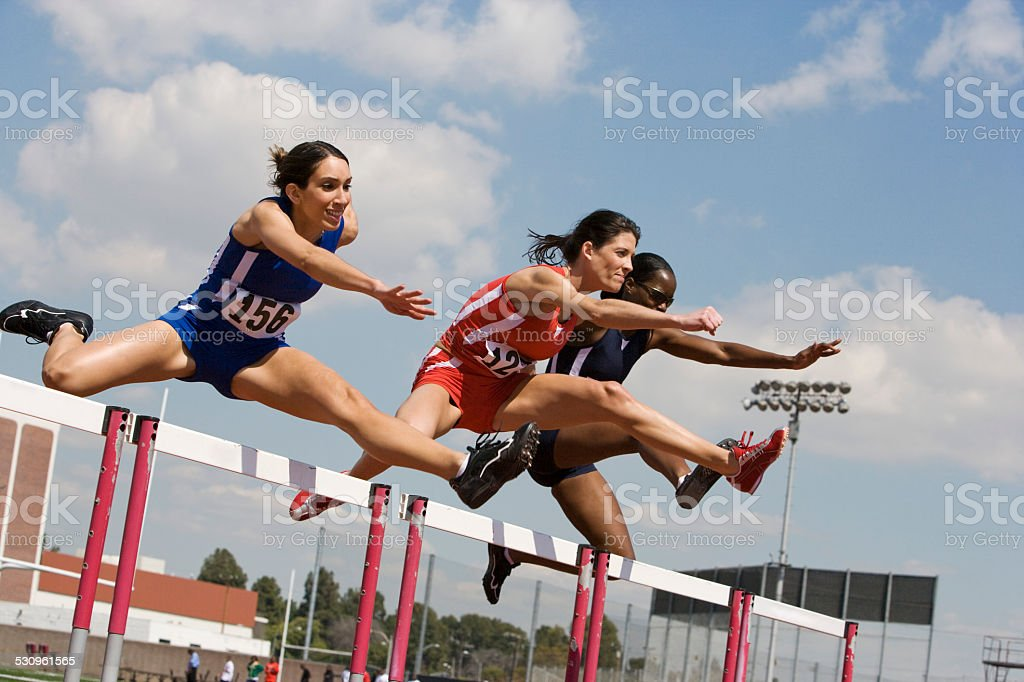 Female athletes hurdling stock photo