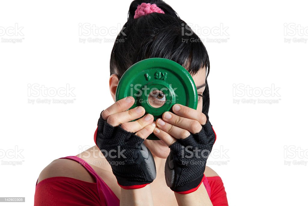 Female athlete's looking through dumbbell disk stock photo