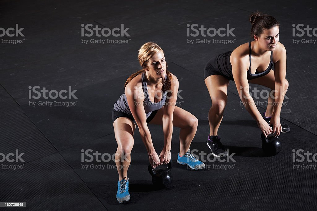 Female athletes working out with kettle bells stock photo