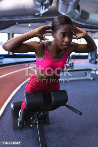 istock Female athletic exercising on ab bench in fitness center 1166608645
