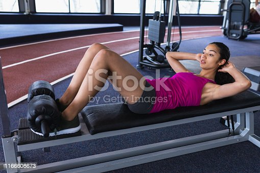 istock Female athletic exercising on ab bench in fitness center 1166608673