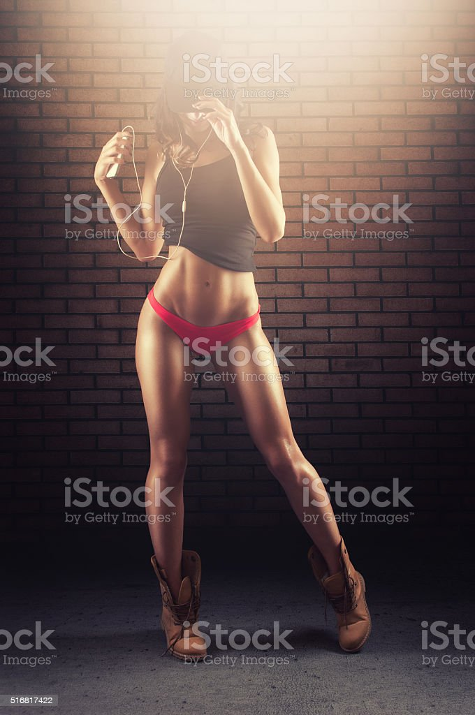 Female athletic model listening to the music stock photo
