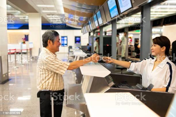 Female attendant giving boarding pass to passenger picture id1161658269?b=1&k=6&m=1161658269&s=612x612&h=u0o gpnpnnsr qvuxzxbmwyirzd57hd1ukevodll zu=