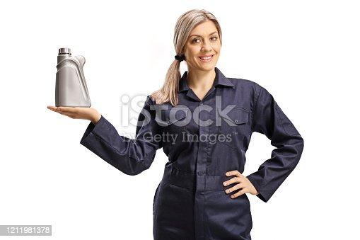 Female auto mechanic holdin a bottle of motor oil isolated on white background