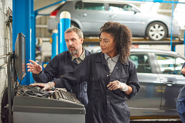 female auto mechanic with her boss stock photo