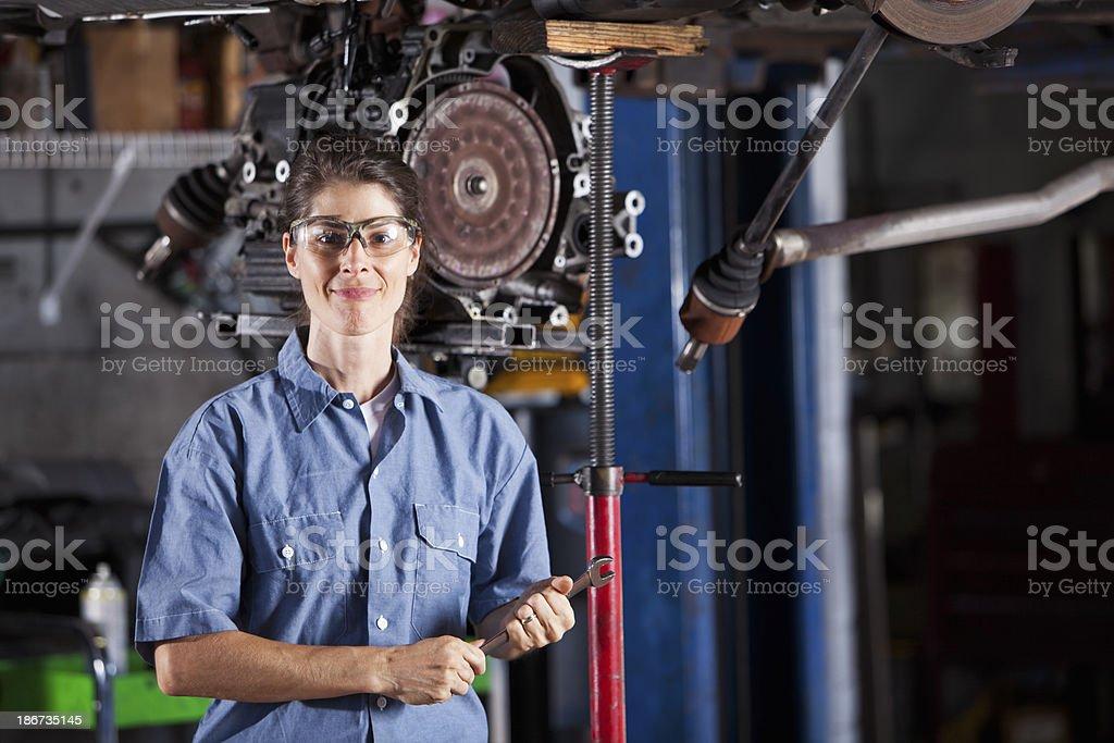 Female auto mechanic working on car transmission stock photo