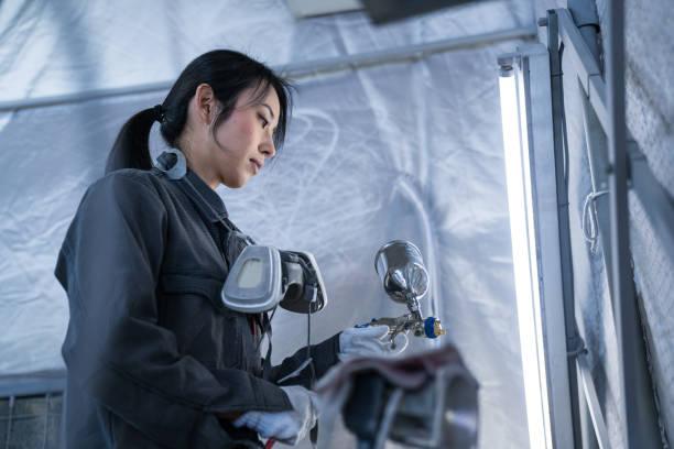 Female autobody technician in an automotive repair shop stock photo