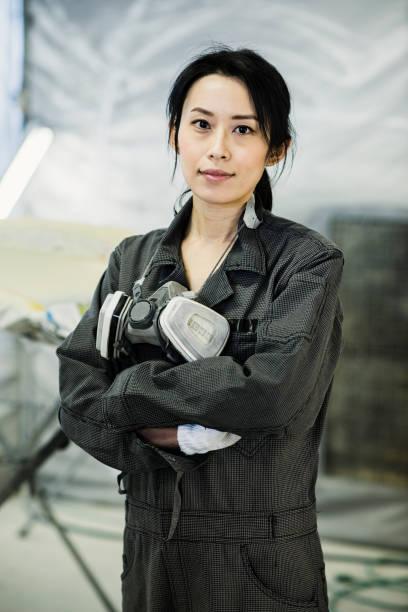Technicien en carrosserie femelle dans un atelier de réparation automobile - Photo