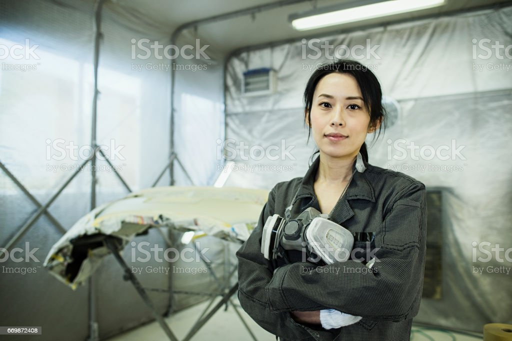 Female autobody technician in an automotive repair shop stock photo