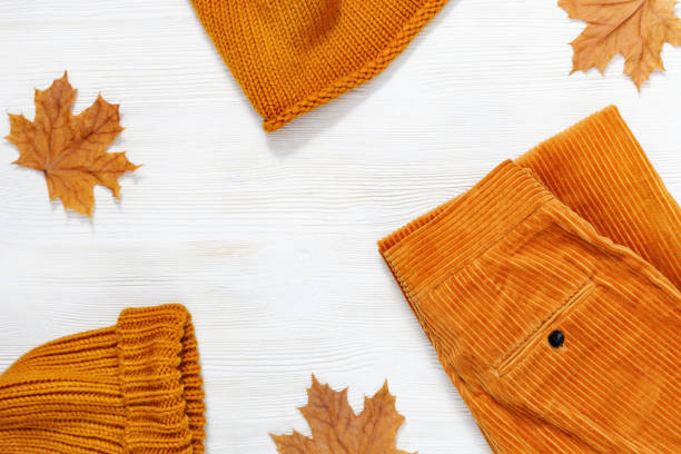 female autumn clothing, warm knitted scarf and cap orange colored and trousers from corduroy. shopping overview concept with copy space. top view. flat lay. - corduroy stock pictures, royalty-free photos & images