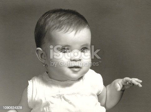 One year old caucasian female baby posing in the sixties