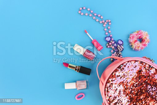 istock Female backpack with cosmetics and women's accessories on blue background. 1133727651