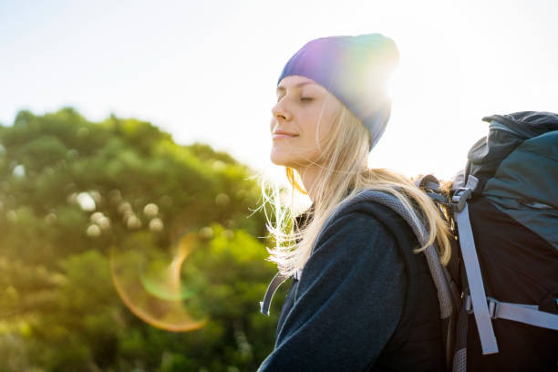 female backpacker meditating on sunny day - medium length hair stock photos and pictures