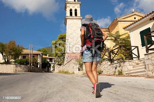 Female backpacker walking in old town in Greece.