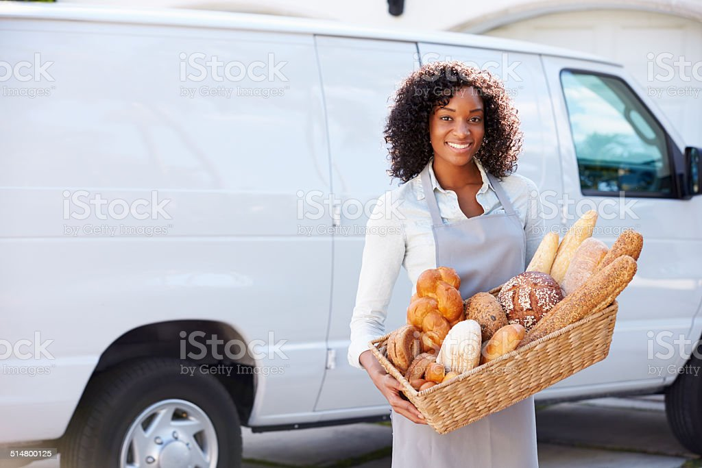 Female Baker Delivering Bread Standing In Front Of Van stock photo