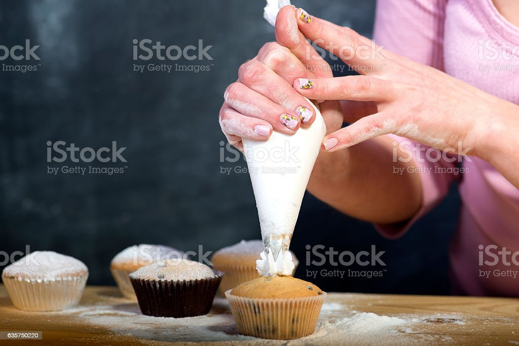 Female baker hands decorating cupcakes stock photo