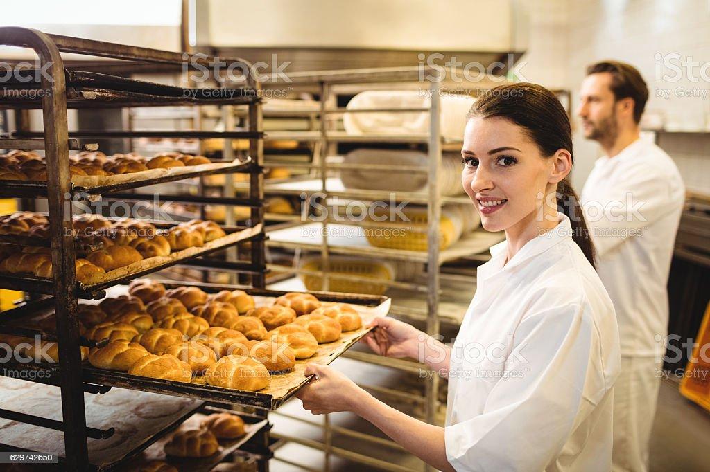 Female baker holding a tray of michetta stock photo