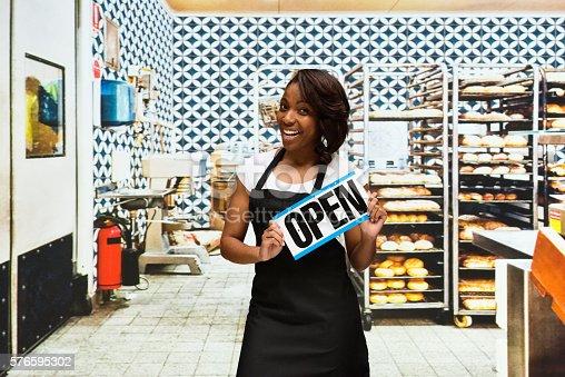 545282128 istock photo Female baker holding open sign in bakery 576595302