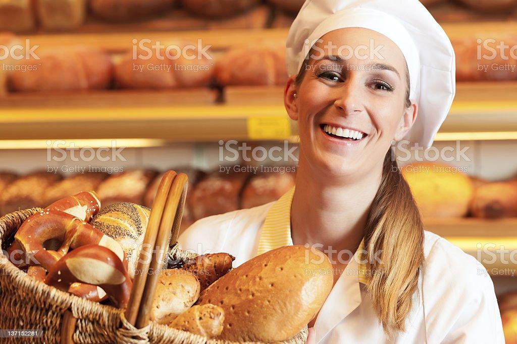 Female baker in bakery selling bread by basket stock photo