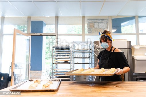 Woman wearing a protective face mask for COVID-19 safety. Female baker making pastries. Reopening the economy after the coronavirus.