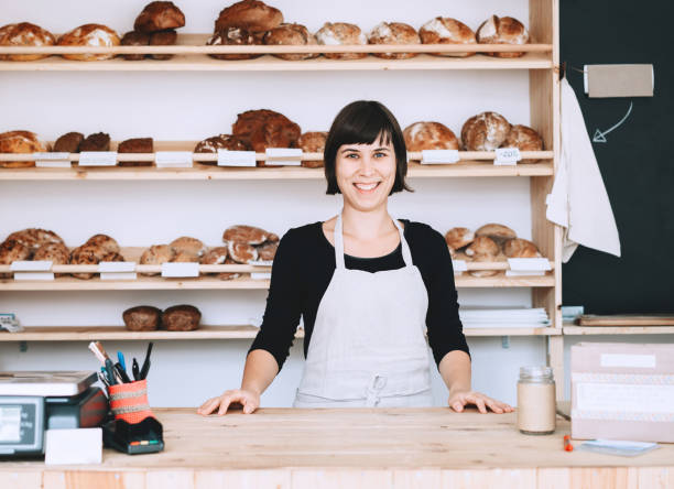 Female bakery worker behind the counter ready to service. Owner small local business. stock photo
