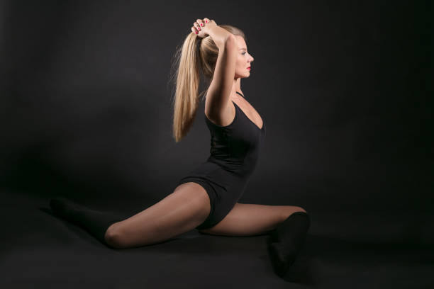 female ballet dancer against black background - leotard stock pictures, royalty-free photos & images