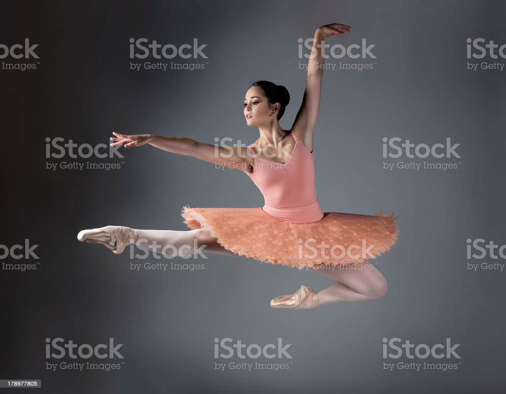 Female ballet dancer in midair during jump on a gray back stock photo