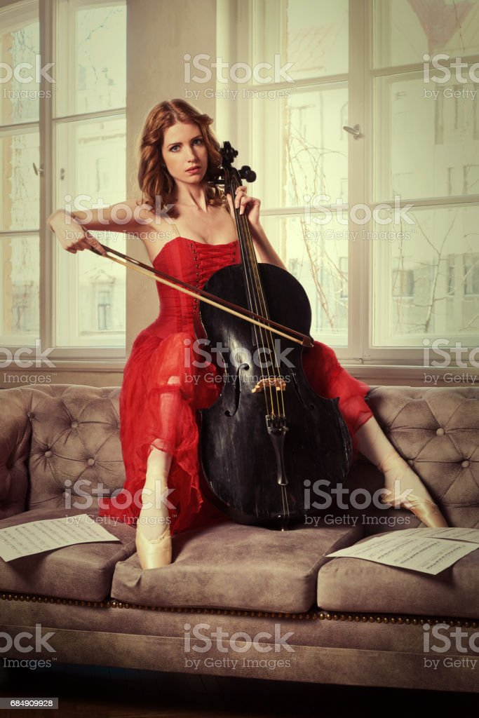 Female Ballet Dancer In Red Dress And Pointe Playing On Antique