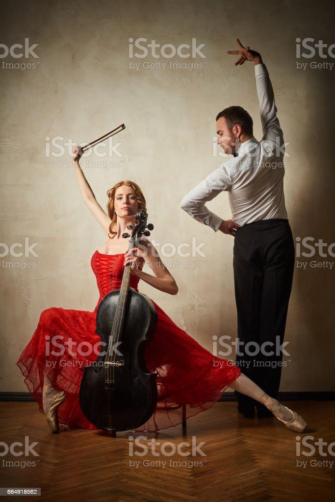 Weibliche Ballett-Tänzerin im roten Kleid und Pointe spielen auf antiken schwarzen Cello und Tanz Latein männlich Lizenzfreies stock-foto