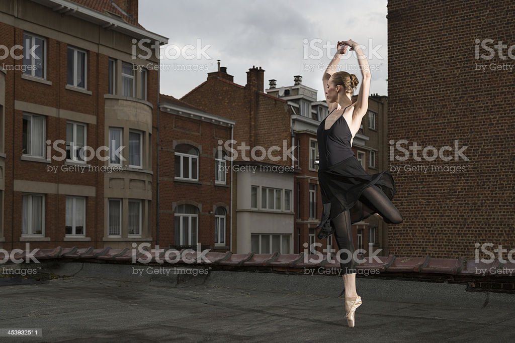 Female ballet dancer performs rotation on a rooftop stock photo