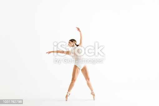 Young female ballet dancer wearing leotard while dancing with grace on white background