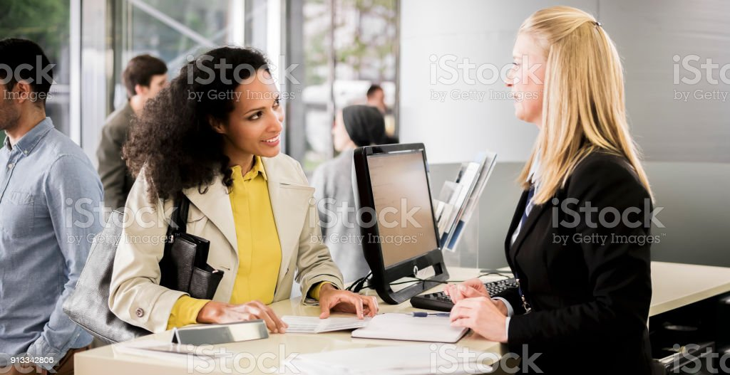 Female bank teller advising female customer stock photo