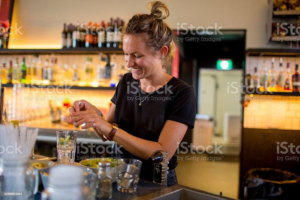 Female bar tender behind bar making a drink stock photo