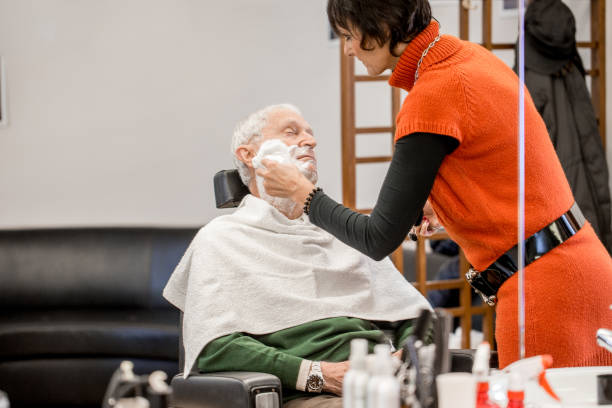 Female Barber Applying Shaving Cream Female Barber Applying Shaving Cream on Senior Man shaving brush shaving cream razor old fashioned stock pictures, royalty-free photos & images