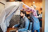 Female barber spreading cape on customer in salon