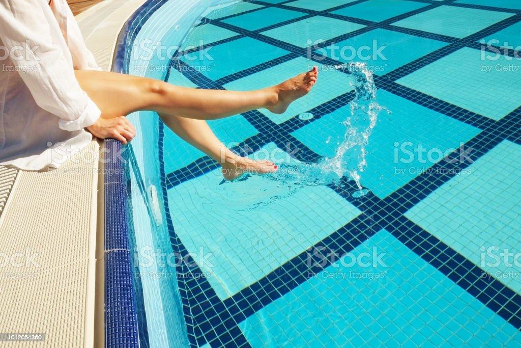 Vrouwelijke blote voeten bij het zwembad. Jonge vrouw rust in de buurt van openlucht zwembad blote voeten. Luxe hotel en spa resort concept. - Royalty-free Beauty spa Stockfoto