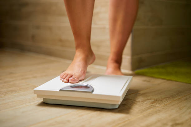 Female bare feet while weighing on scale weight stock photo