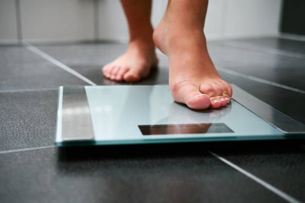 Female bare feet with weight scale stock photo
