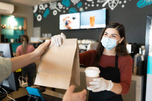 weibliche barista gibt paket und kaffee an kunden - coffee shop stock-fotos und bilder