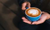 Female barista hands holding cup of fresh delicious cappuccino with latte art cream foam, brewed and made with love and take care concept, good service coffee shop