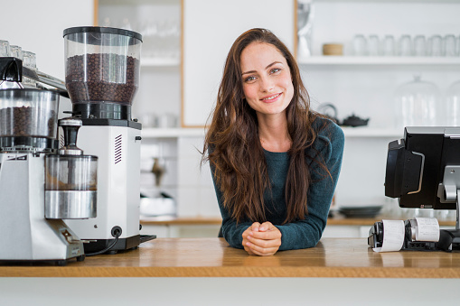 istock Female barista leaning on counter in coffee shop 538177378