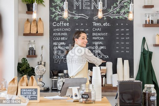Pretty Hispanic female barista looks over her shoulder while working on a customer's coffee order.